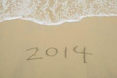 Jaar 2014 hand die op wit zand i wordt geschreven Stock Fotografie