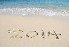 Jaar 2014 hand op het witte zand wordt geschreven dat Royalty-vrije Stock Fotografie