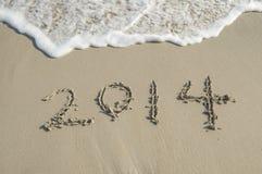 Jaar 2014 hand op wit zand i wordt geschreven die Royalty-vrije Stock Foto's