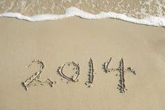 Jaar 2014 hand op wit zand i wordt geschreven die Stock Afbeeldingen