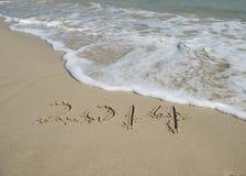 Jaar 2014 hand op wit zand i wordt geschreven die Stock Afbeelding
