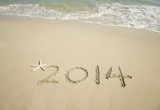 Jaar 2014 hand op wit zand i wordt geschreven die Royalty-vrije Stock Foto