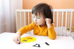 2 jaar jongen gemaakt gezichts van document details Stock Fotografie