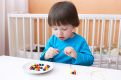 2 jaar jongens in blauw overhemd gemaakt tot multicolored parels Stock Afbeelding