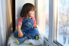 2 jaar jongens zit op vensterbank en kijkt uit venster in wintertijd Stock Foto