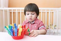 2 jaar jongensspelen met wasknijpers Stock Fotografie