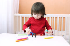 2 jaar kind in rood overhemd met playdough Royalty-vrije Stock Fotografie