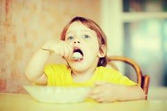 2 jaar kind zelf eet zuivelfabriek Stock Afbeeldingen