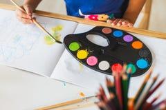 3 jaar meisje het schilderen bij de kleine lijst thuis stock foto's