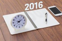 Jaar 2016 met notitieboekje en klok op houten lijst Stock Fotografie