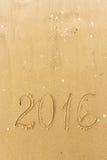 2016 Jaar op het strandzand dat wordt geschreven Stock Foto's