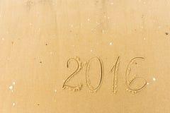 2016 Jaar op het strandzand dat wordt geschreven Stock Afbeelding
