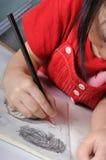 3 jaar oud Aziatisch meisjes trekt en sketchs vele menselijke gezichten met p Royalty-vrije Stock Afbeelding