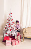 8 jaar oud meisje dieKerstboom thuis verfraaien Stock Afbeelding