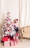 8 jaar oud meisje dieKerstboom thuis verfraaien Stock Foto's