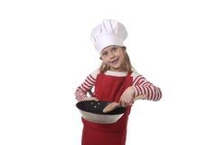 6 of 7 jaar oud meisje in het koken van hoed en rode schort speelkok die gelukkige holdingspan en lepel glimlachen Stock Fotografie