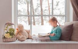 3 jaar oud meisjes die leren te lezen Stock Foto