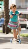 4 jaar oud meisjes die met autoped blijven Stock Afbeelding