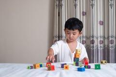 3 jaar oud weinig leuk Aziatisch stuk speelgoed van het jongensspel of vierkant blok puzzl Stock Afbeelding