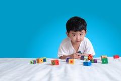 3 jaar oud weinig leuk Aziatisch stuk speelgoed van het jongensspel of vierkant blok puzzl Stock Fotografie