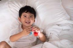 3 jaar oud weinig leuke Aziatische jongen thuis op het bed, jong geitje het liggen Stock Foto's