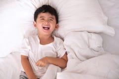 3 jaar oud weinig leuke Aziatische jongen thuis op het bed, jong geitje het liggen Stock Afbeeldingen