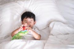 3 jaar oud weinig leuke Aziatische jongen thuis op het bed, jong geitje het liggen Royalty-vrije Stock Afbeelding