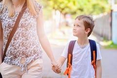 7 jaar oude jongens die naar school met zijn moeder gaan Stock Foto