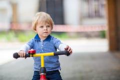 2 jaar oude peuter die op zijn eerste fiets berijden Stock Afbeelding