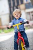 2 jaar oude peuter die op zijn eerste fiets berijdt Stock Afbeeldingen