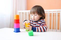 2 jaar peuter die plastic blokken thuis spelen Stock Foto's