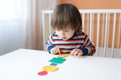 2 jaar peuter het spelen met geometrische cijfers thuis Royalty-vrije Stock Foto