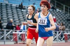 70 jaar stellen de oude vrouwen 100 meters in werking Stock Foto