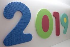 Jaar 2019 verder weg geschreven met peuterstuk speelgoed aantallen op witte achtergrond met nummer twee in de voorzijde en 9 stock fotografie