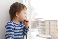 1 jaarbaby die uit venster kijken Stock Foto