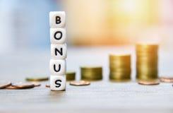 Jaarlijkse Bonusconcept/woorden van Bonus en Stapelmuntstukken op achtergrond voor Aanmoedigingsmoreel op het lijstbureau royalty-vrije stock foto's