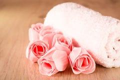 Jabón bajo la forma de rosas y toalla en un fondo de madera Foto de archivo