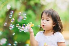 Jabón de las burbujas del niño que sopla lindo en el jardín fotos de archivo