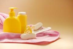 Jabón del bebé, polvo de talco, cepillos y pacificador en una toalla rosada imagenes de archivo