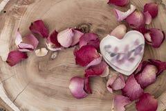 Jabón en la forma del corazón entre los pétalos color de rosa en el fondo de madera Fotos de archivo libres de regalías
