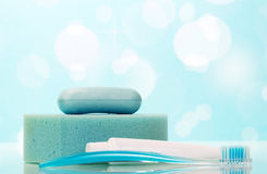 Jabón, goma de diente y cepillo en cuarto de baño en azul abstracto Imágenes de archivo libres de regalías