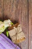 Jabón hecho a mano orgánico, toalla púrpura de la sauna y flores en el fondo del árbol de nuez, disposición con el espacio del te Foto de archivo libre de regalías