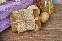 Jabón orgánico, toalla púrpura de la sauna y decoración en el fondo del árbol de nuez, disposición con el espacio del texto libre Imagen de archivo libre de regalías