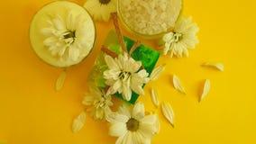 Jabón, sal, flor del crisantemo en un fondo coloreado metrajes