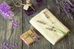 Jabón, sal y tinte hechos a mano de la lavanda, toalla del mar en superficie de madera fotografía de archivo