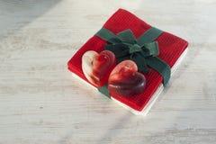 Jabón translúcido rojo de los pares del corazón de la tarjeta del día de San Valentín en la toalla roja Imágenes de archivo libres de regalías