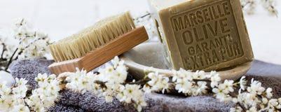 Jabón verde con aceite de oliva sobre la toalla y las flores frescas Fotos de archivo libres de regalías
