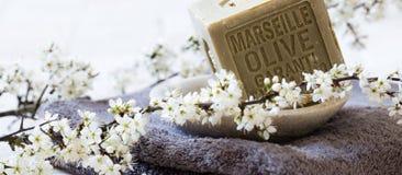 Jabón verde con aceite de oliva sobre la toalla y las flores frescas Imagen de archivo