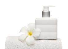 Jabón y flor cuadrados de la botella en el fondo blanco del blanco de la toalla Foto de archivo