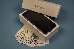 Jabłczani iPhone przyrząda, dolary na błękitnym monophonic tle i Voronezh Rosja, Maj, - 3, 2019 fotografia stock